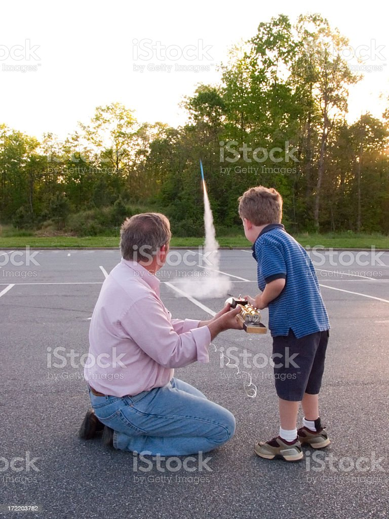 Grandfather and child launch model rocket royalty-free stock photo