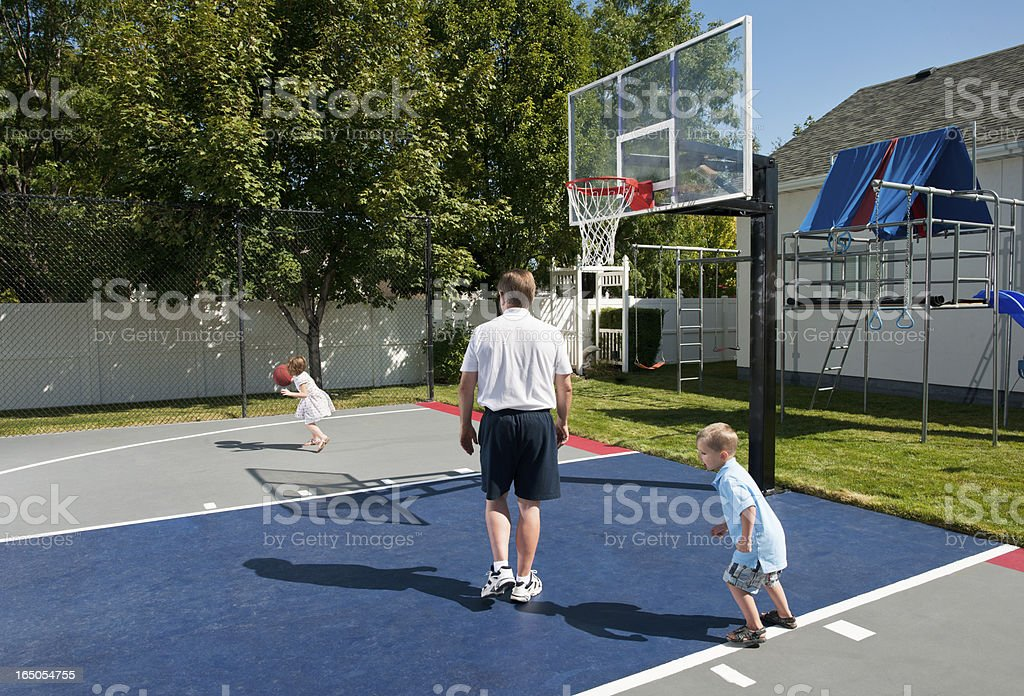 Grandfather And Grand Children Playing Basketball stock photo