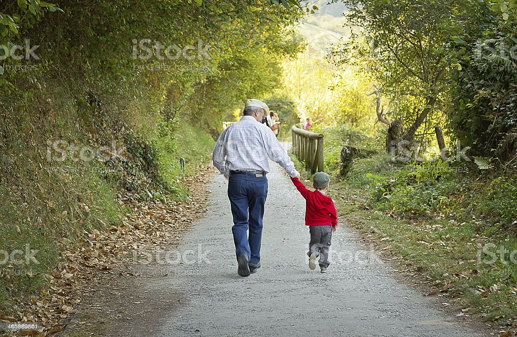 Grandfather and grandchild walking in nature path stock photo