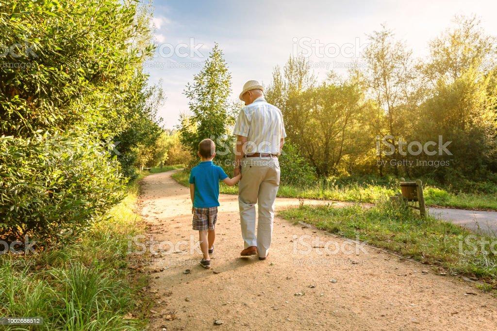 Abuelo y nieto caminando al aire libre - foto de stock