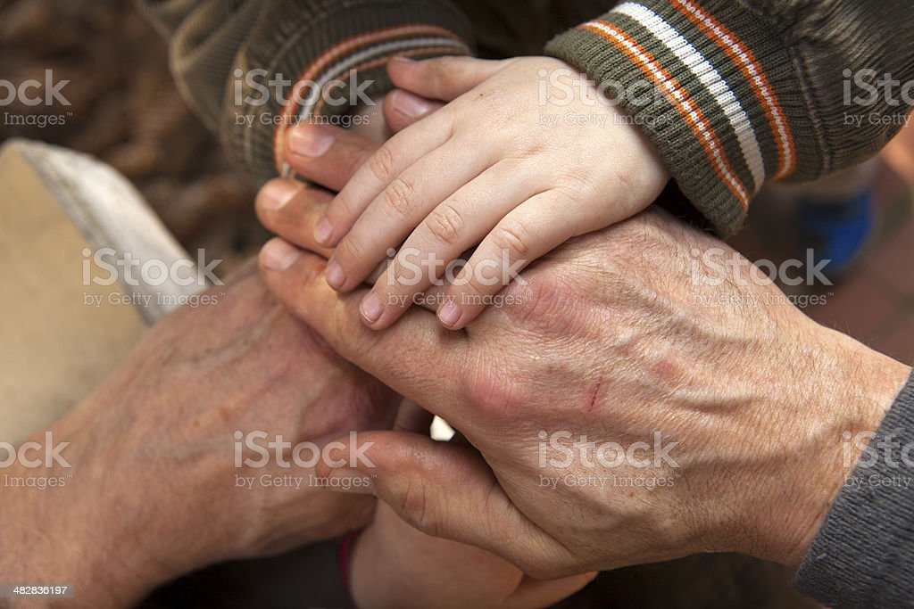 Grandfather and grandchildren playing hands stock photo