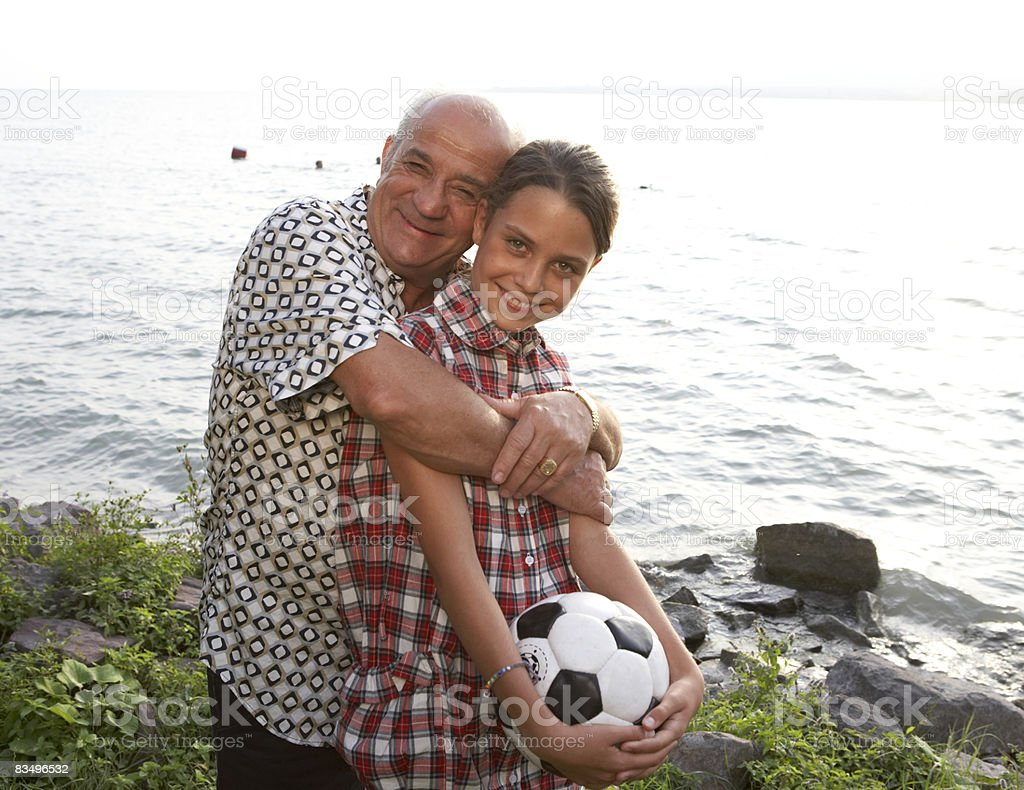 grandfather and granddaughter by a lake royalty-free stock photo