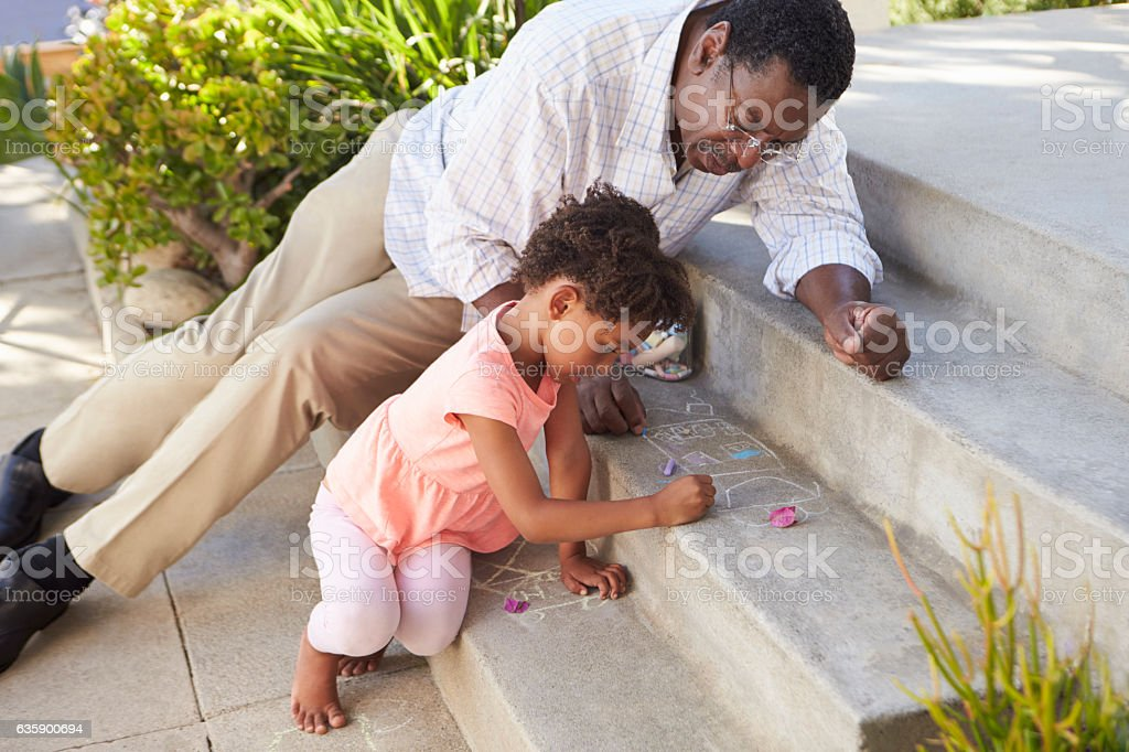 Grandfather And Granddaughter Drawing Picture On Steps stock photo