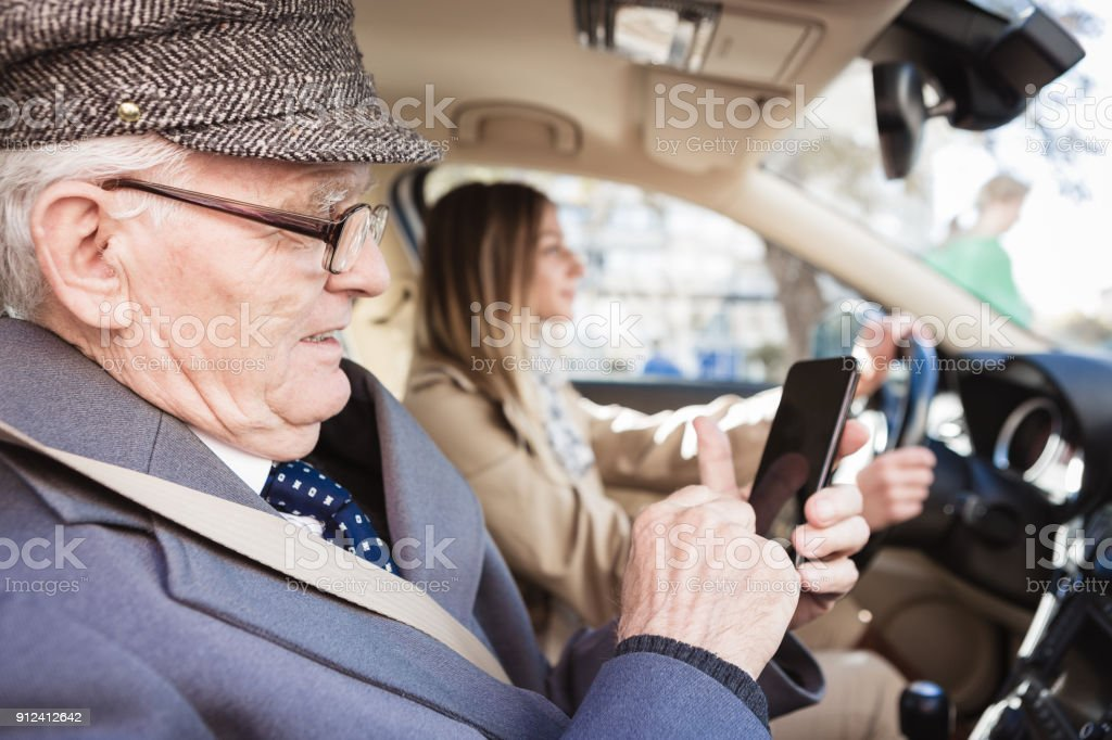 Grandfather and granddaughter driving by the car. He is using mobile phone stock photo