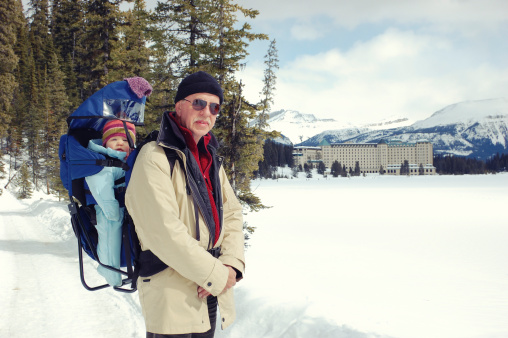 Grandfather and granddaughter hiking on a frozen Lake Louise, Canada