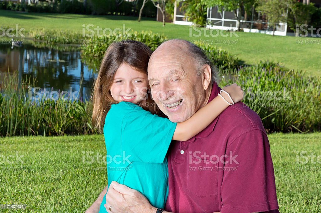 Grandfather and granddaughter hugging stock photo