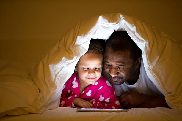Grandfather And Granddaughter In Bed stock photo