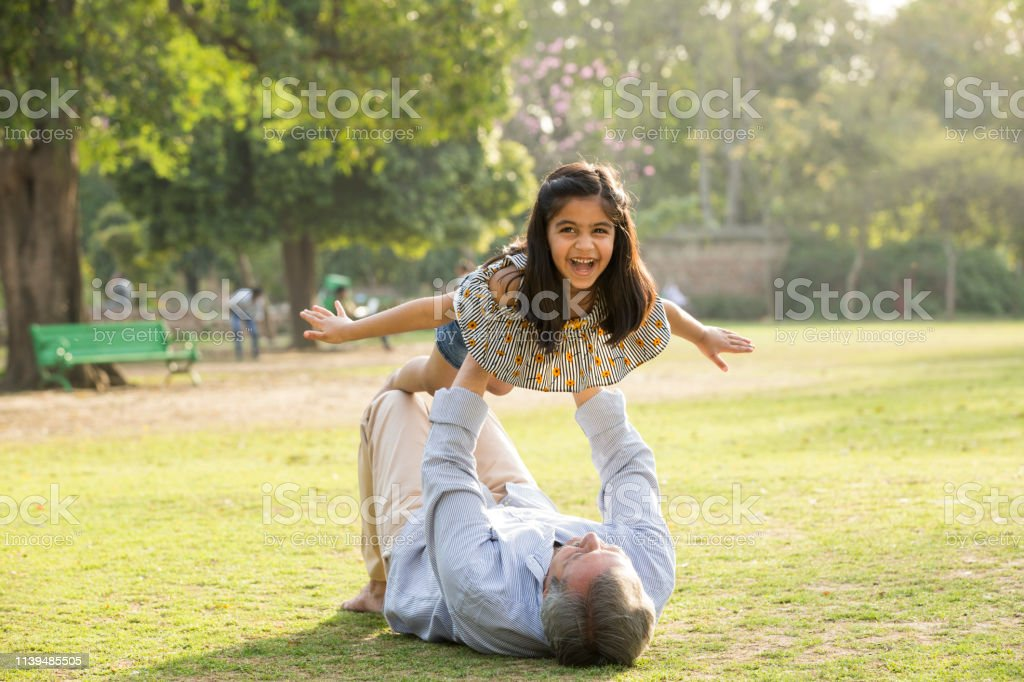 Grandfather And Granddaughter In Garden Stock Photo -1460