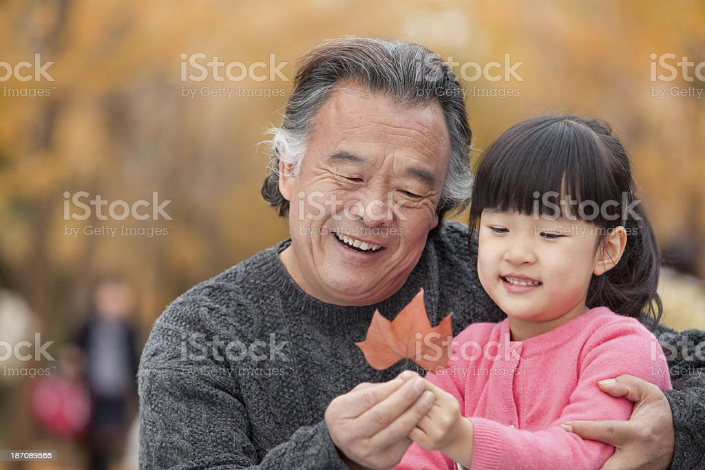 Grandfather and granddaughter in park stock photo