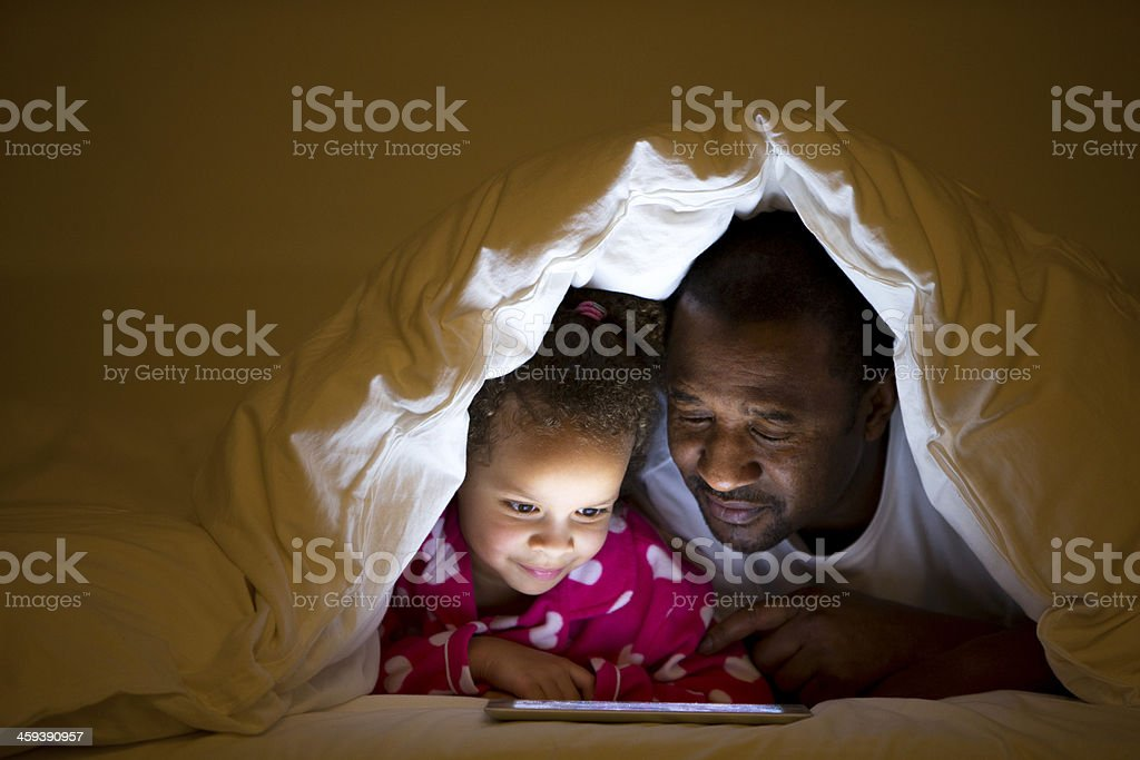 Grandfather and Granddaughter lying in bed stock photo