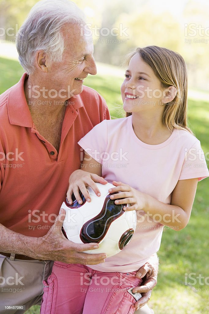 Grandfather and granddaughter outdoors with ball smiling royalty-free stock photo