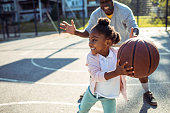 Close up of a grandfather taking his granddaughter to play some basketball in the park