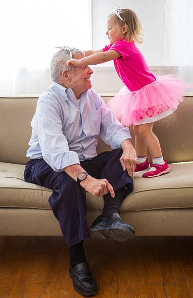 großvater und enkelin fröhliches anprobieren - prinzessinnen tutu stock-fotos und bilder