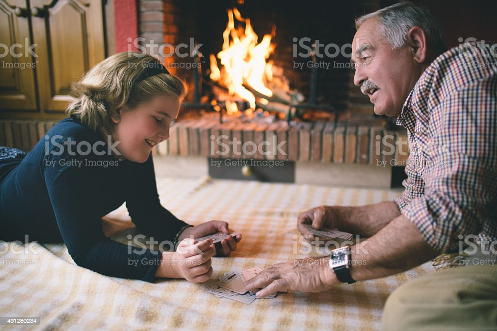Grandfather and granddaughter playing cards stock photo