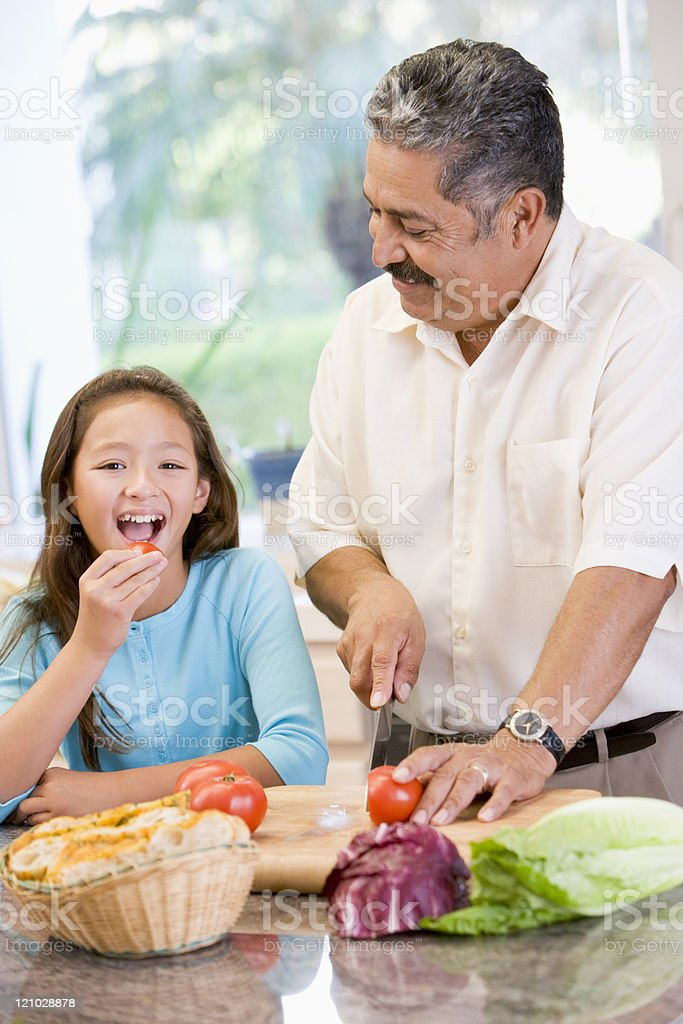 Grandfather And Granddaughter Preparing Meal Together stock photo