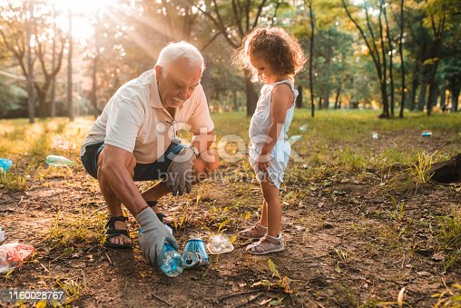 Grandfather and granddaughter picking up water bottles and recycling