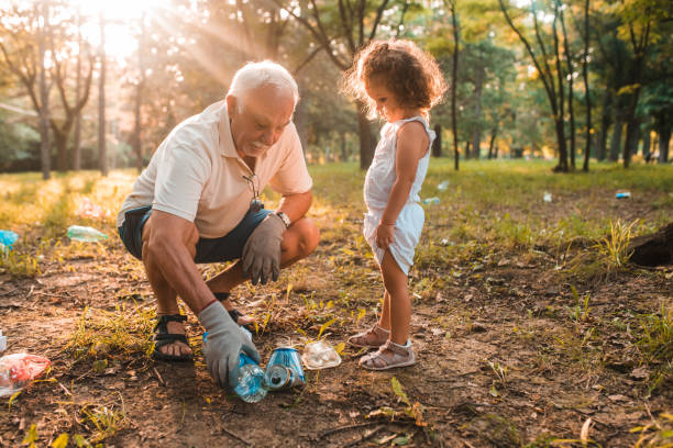 Grandfather and granddaughter recycling stock photo