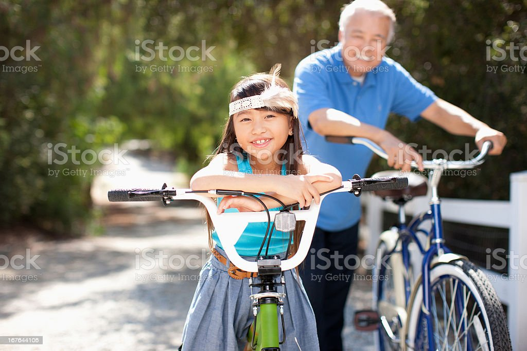 Grandfather and granddaughter riding bicycles outdoors royalty-free stock photo
