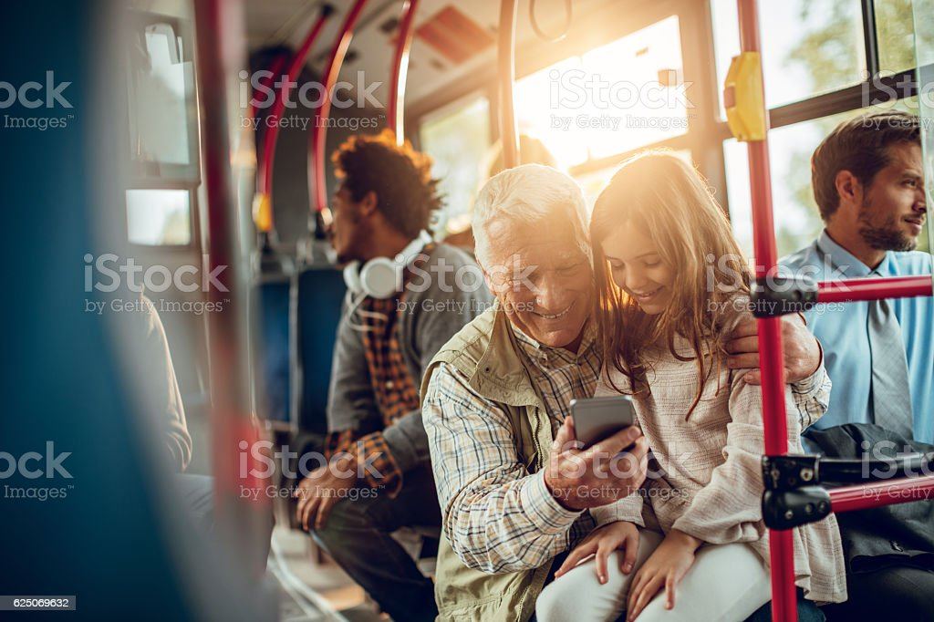 Grandfather and granddaughter riding in a bus stock photo