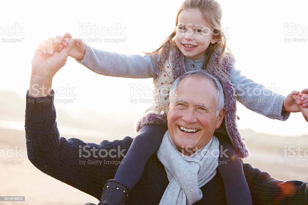 Grandfather And Granddaughter Walking On Winter Beach stock photo