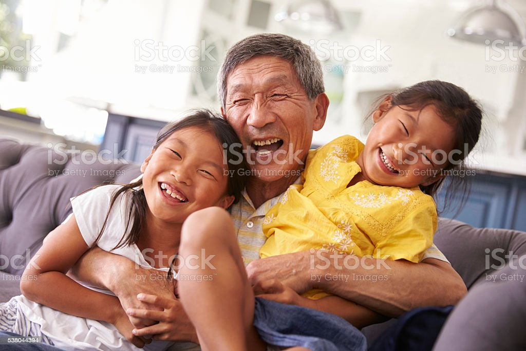 Grandfather And Granddaughters Relaxing On Sofa At Home stock photo