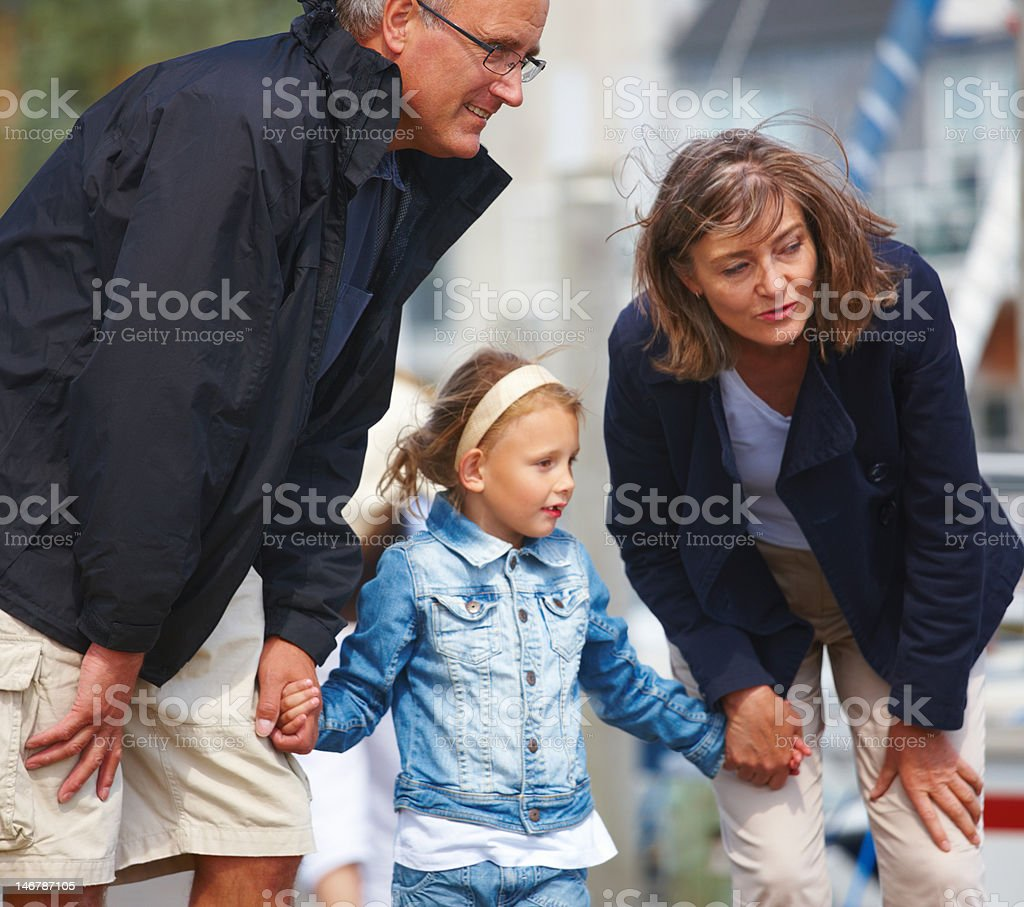 Grandfather and grandmother holding hands of granddaughter on street royalty-free stock photo
