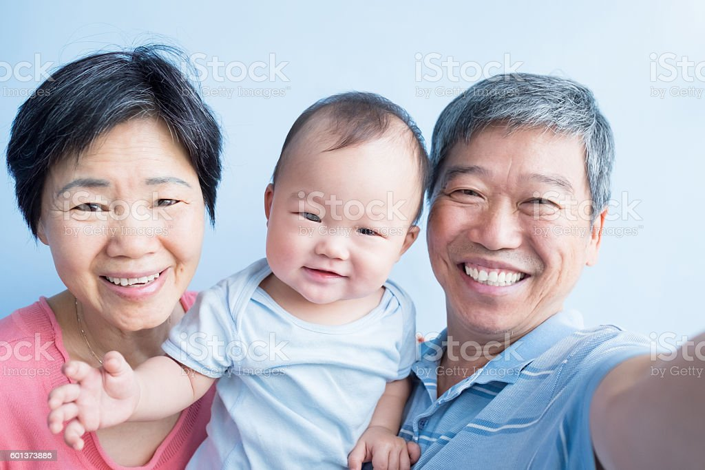 grandfather and grandmother hug grandson stock photo