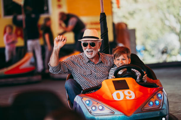 Grandfather and grandson amusement park fun Grandfather and grandson having fun and spending good quality time together in amusement park. They enjoying and smiling while driving bumper car together. grandson stock pictures, royalty-free photos & images