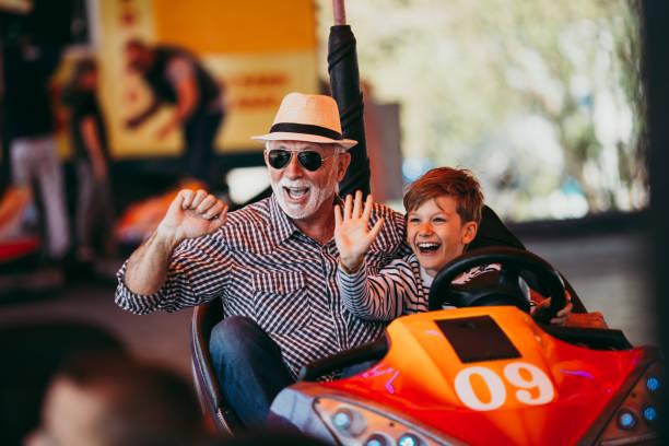 grandfather and grandson amusement park fun - luna park foto e immagini stock