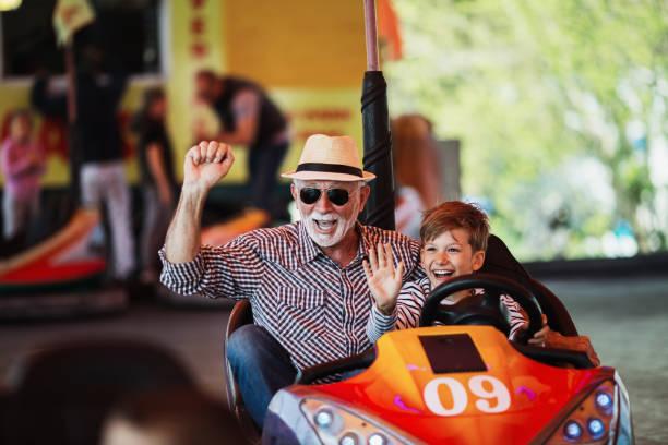 grootvader en kleinzoon amusement park fun - mini amusementpark stockfoto's en -beelden