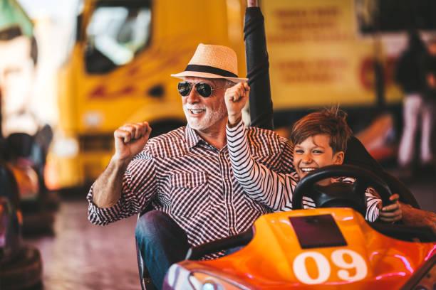 grootvader en kleinzoon pretpark fun - mini amusementpark stockfoto's en -beelden