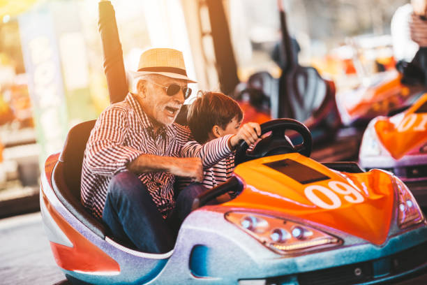 Grandfather and grandson amusement park fun Grandfather and grandson having fun and spending good quality time together in amusement park. They enjoying and smiling while driving bumper car together. amusement park stock pictures, royalty-free photos & images