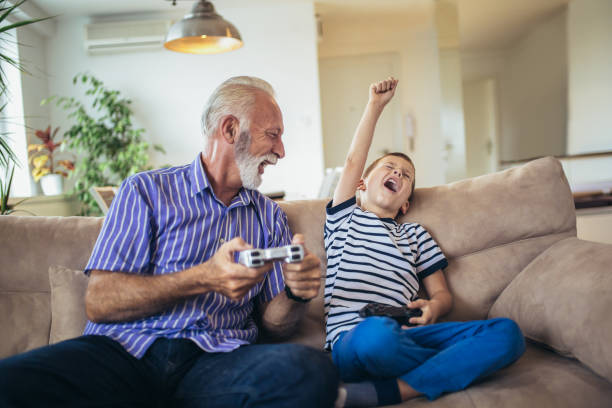 Grandfather and grandson are playing video games at home. Grandfather and grandson are playing video games at home. grandson stock pictures, royalty-free photos & images