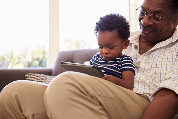 Grandfather And Grandson At Home Using Digital Tablet stock photo