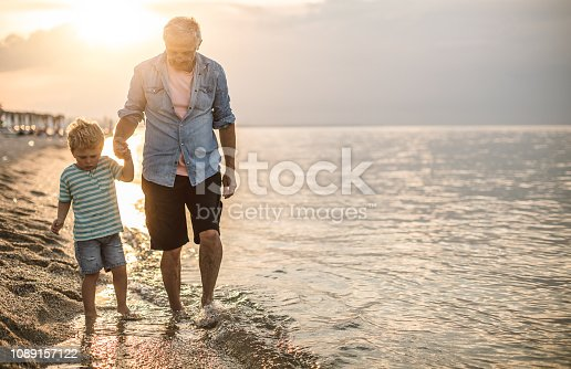 istock Grandfather and grandson at the beach 1089157122