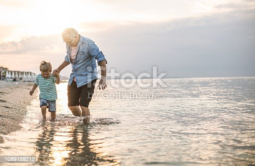 Grandfather and grandson walking at the beach on sunset
