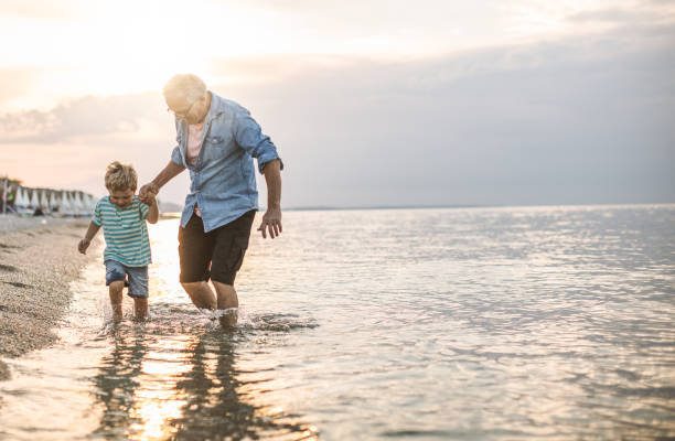Grandfather and grandson at the beach Grandfather and grandson walking at the beach on sunset grandson stock pictures, royalty-free photos & images