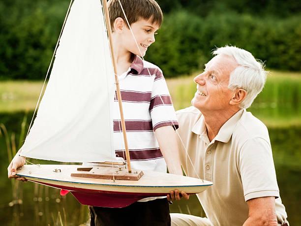 großvater und enkel im park - teichfiguren stock-fotos und bilder
