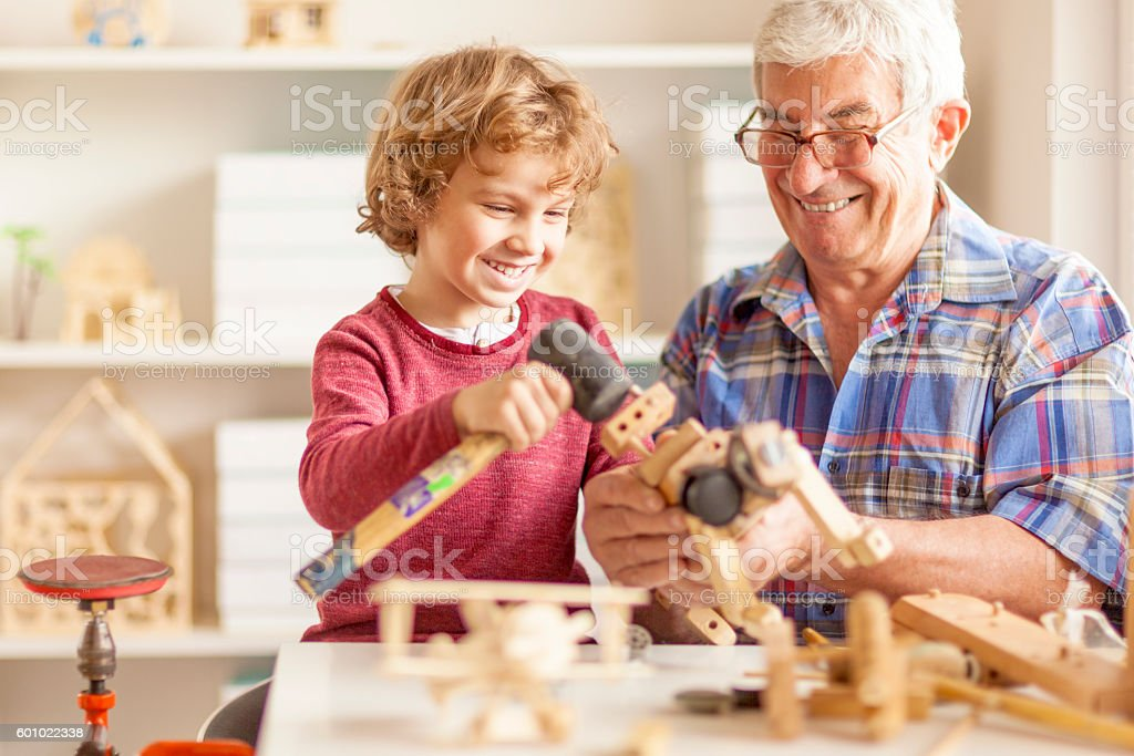 Grandfather and grandson crafting wooden toys stock photo