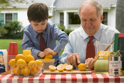 Grandfather and grandson cutting lemons for lemonade