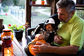 A young boy in a skeleton costume is sitting on the porch with his grandfather and drawing a face on a Halloween pumpkin