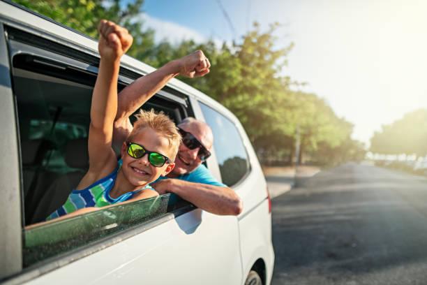 grand-père et petit-fils pendant le voyage routier - homme faire coucou voiture photos et images de collection