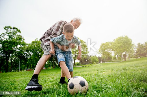639800036istockphoto Grandfather and grandson enjoy a game 1154361930