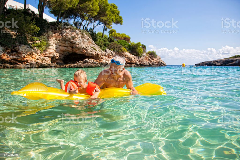 Grandfather and grandson enjoying sea with floatation device royalty-free stock photo