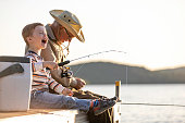 A grandfather is teaching his grandson to fish during sunset in summer. They are both sitting on the dock and laughing. It is a beautiful summer day. Across the lake, there is a mountain.