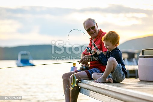 A grandfather is teaching his grandson to fish during sunset in summer. They are both sitting on the dock and are concentrated on their activity. The little redhead boy caught a fish and he is smiling and very happy. It is a beautiful summer day. Across the lake, there is a mountain.