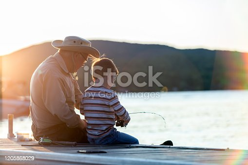 A grandfather is teaching his grandson to fish during sunset in summer. They are both sitting on the dock and are concentrated on their activity. It is a beautiful summer day. Across the lake, there is a mountain.