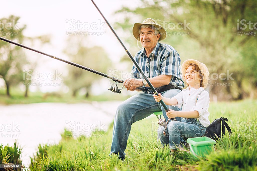 Grandfather and grandson fishing by the river stock photo