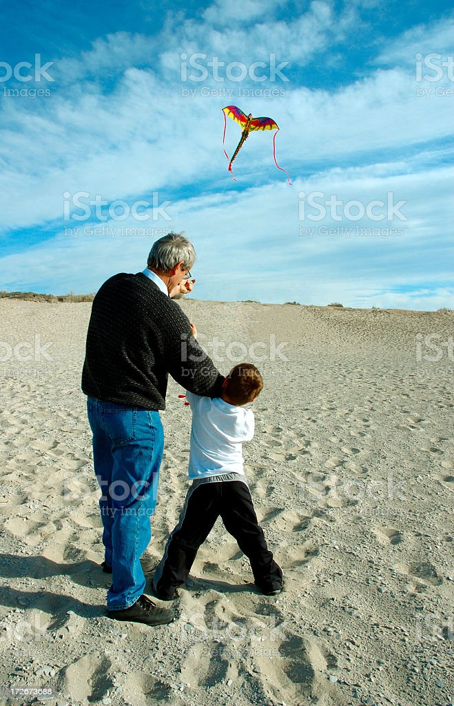 Grandfather and grandson flying a kite on the beach royalty-free stock photo