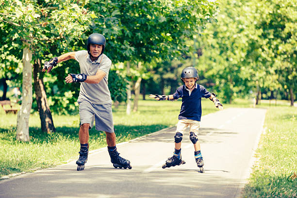 Grandfather and grandson having fun roller skating in the park stock photo